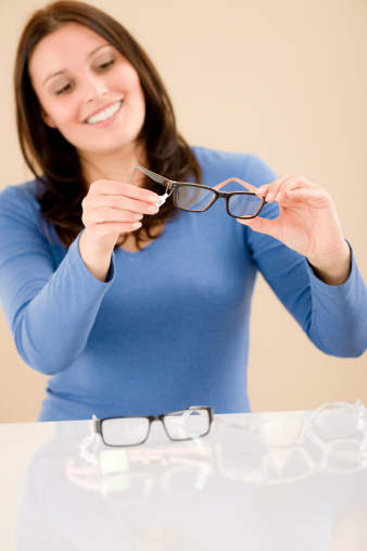A woman looking at her glasses